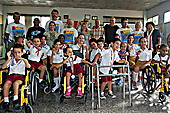 Students showing off their medals with School director Esther María La Ochoa, Gerardo Hernández, and cyclists on the 2015 Cuba Cycle Challenge