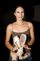 Candy Costa Aguilera, dancer, teacher and choreographer for Ballet Santiago holds up a worn-out, threadbare pair of ballet shoes
