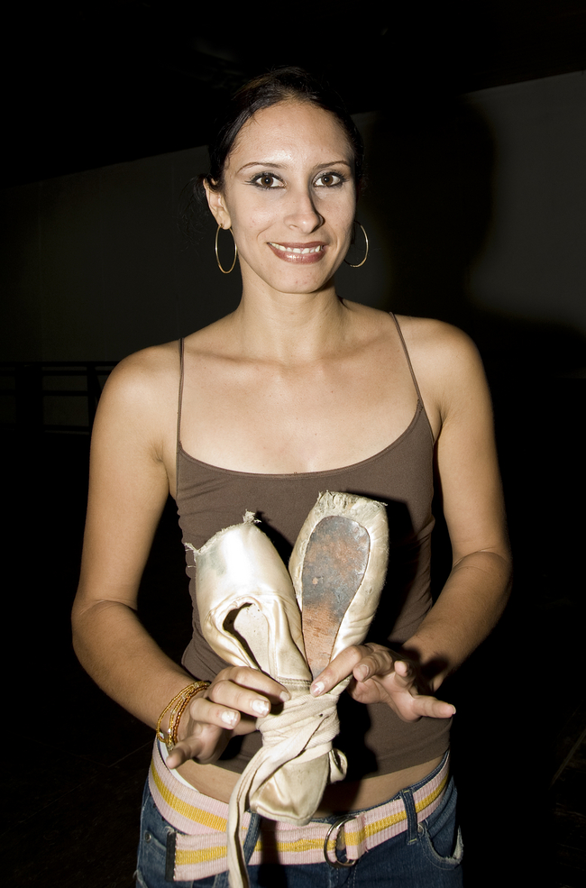 "Candy Costa Aguilera, dancer, teacher and choreographer for Ballet Santiago holds up a worn-out, threadbare pair of ballet shoes:  ""this is what the dancers were using before the donation of shoes c"
